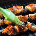 brushing bbq sauce on chicken on a grill with a green brush