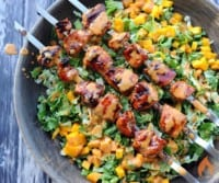 skewers of grilled chicken atop lettuce and mango