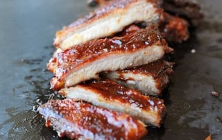 sliced sauced St. Louis Style ribs in a vertical row on black slate
