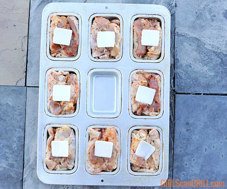 8 chicken thighs in 9-cavity muffin tin with butter on top