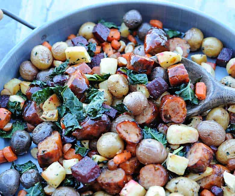 wooden spoon scooping out roasted veggies