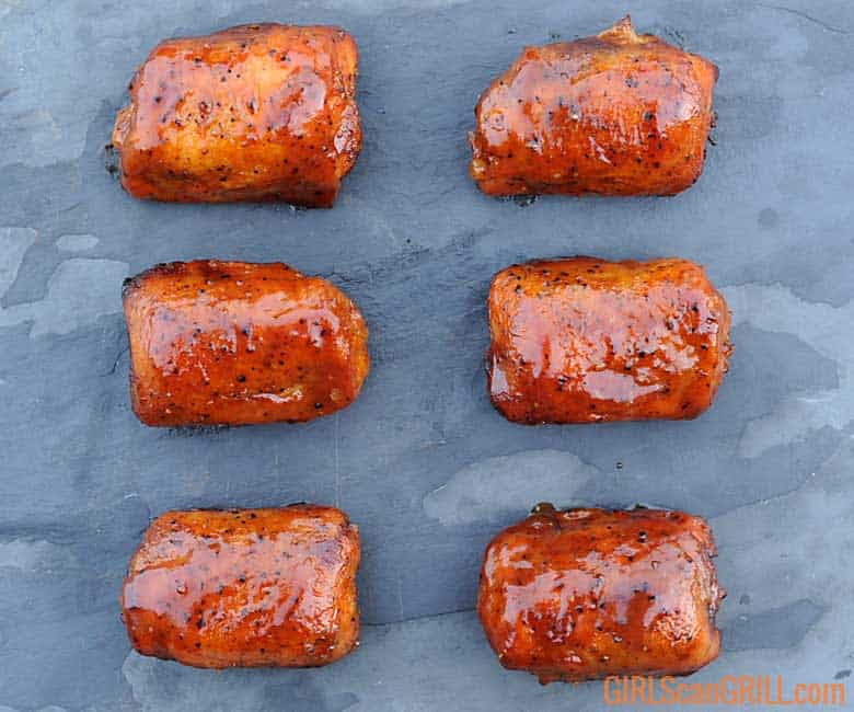 six cooked chicken thighs in two columns on black slate