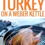 a whole turkey smoking on a black Weber kettle grill
