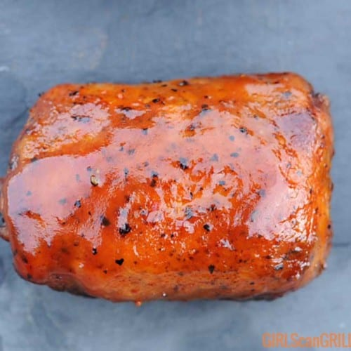a close-up of a cooked, sauced competition chicken thigh on slate