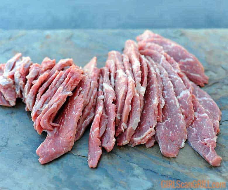 sliced tri-tip beef on a slate platter
