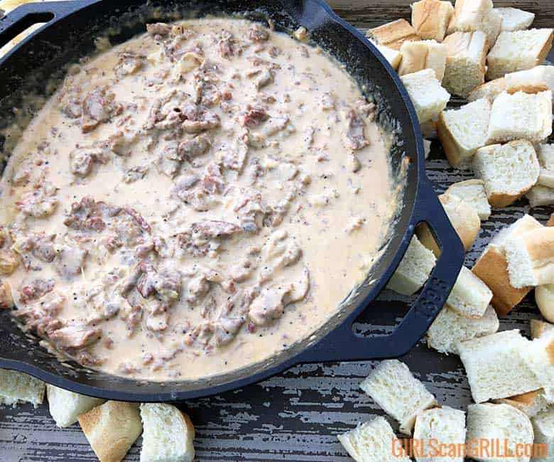 skillet of philly cheesesteak dip alongside bread cubes