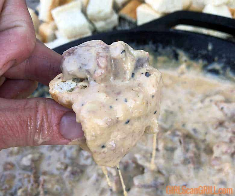 hand holding bread cube dunked in Philly cheesesteak dip