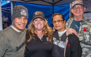 two men and two women posing for photo under tent