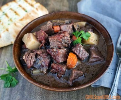 wooden bowl full of pot roast with grilled bread