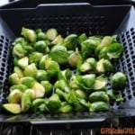 black veggie basket filled with quartered brussels sprouts