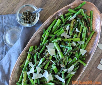 oval shaped copper dish with grilled asparagus inside with jar of capers in top left