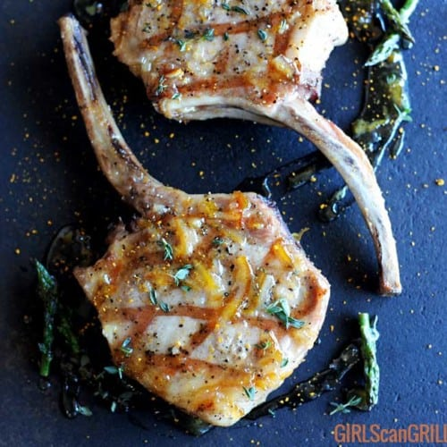 grilled pork chop on black plate with circle of glaze and asparagus
