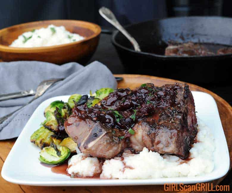 white plate with lamb chop atop white grits, brussels sprouts to left