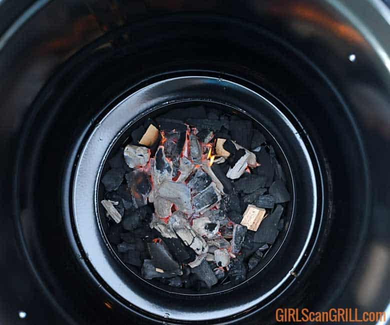 coal basket filled with lit lump charcoal and 3 wood chunks with barrel on top