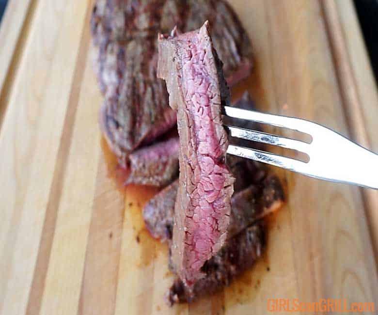 medium rare slice of flat iron steak on a fork