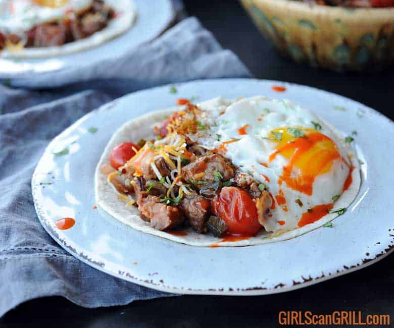 white plate with tortilla, beef, salsa and egg