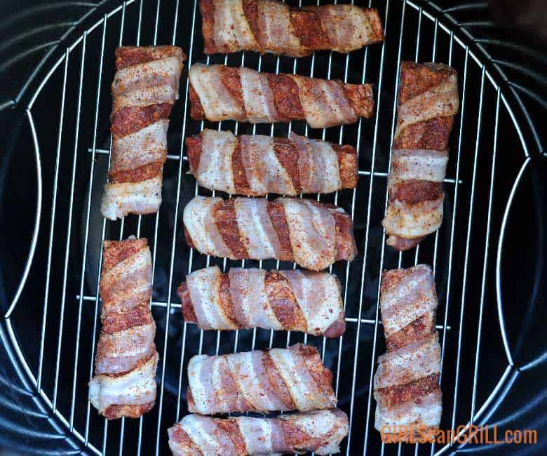 single rib bones wrapped in bacon on grill