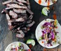 slate platter of sliced pork steak and three tacos with purple cabbage