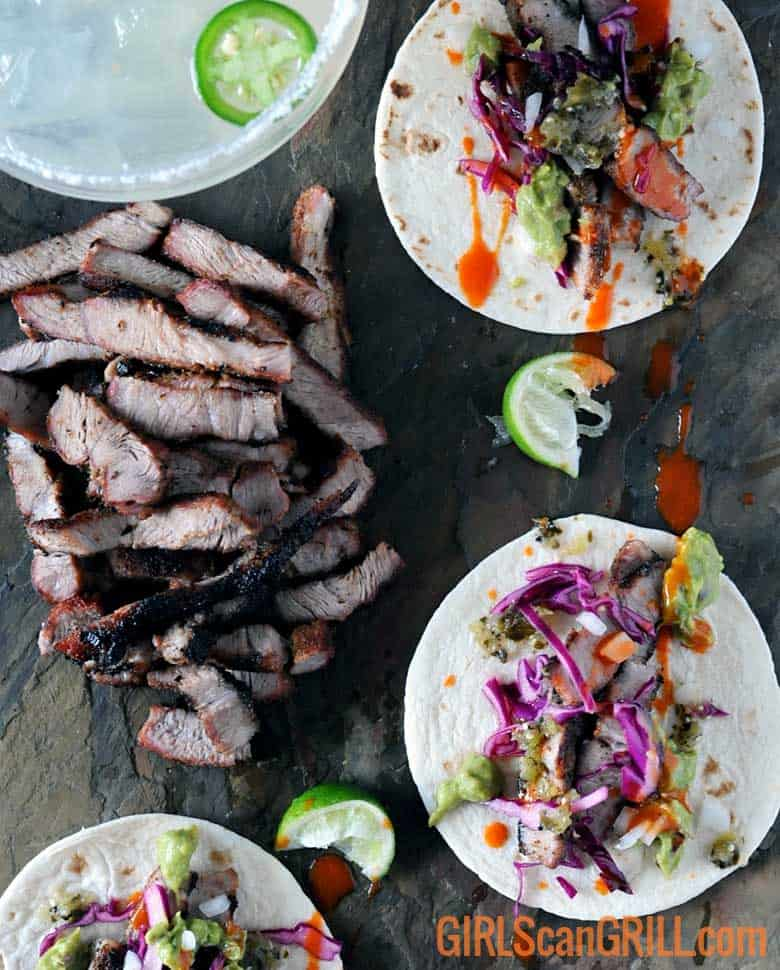 slate platter of sliced pork steak and tacos with purple cabbage