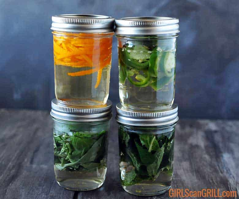 4 jars with herbs and simple syrup