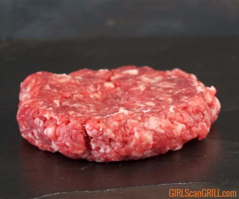 ground ribeye shaped into a burger patty on a slate background