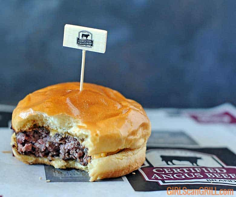 ribeye burger on brioche bun with bite taken out with toothpick