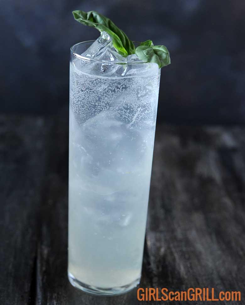 tall narrow glass of smoked basil tom collins with basil sprig