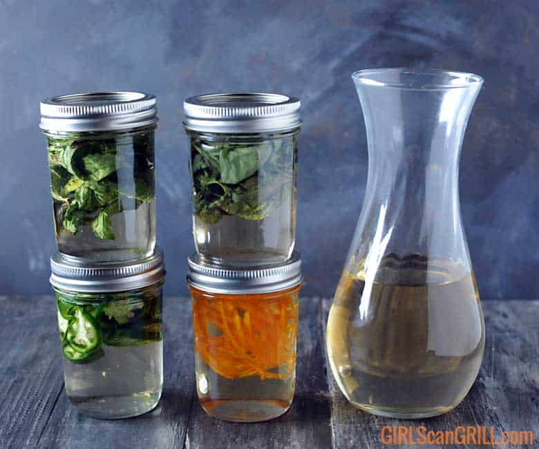 4 jars with herbs and simple syrup near glass vase for smoked cocktails