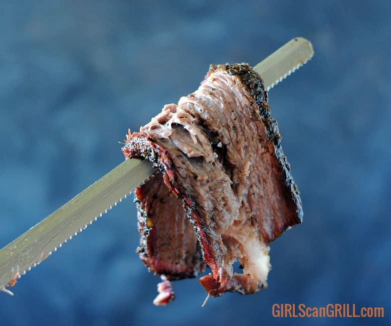 a brisket knife hanging off a serrated knife