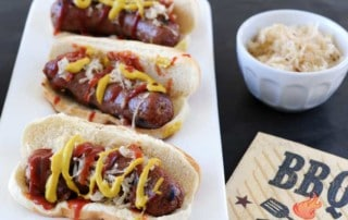 3 bratwurst on a white plate with mustard and ketchup