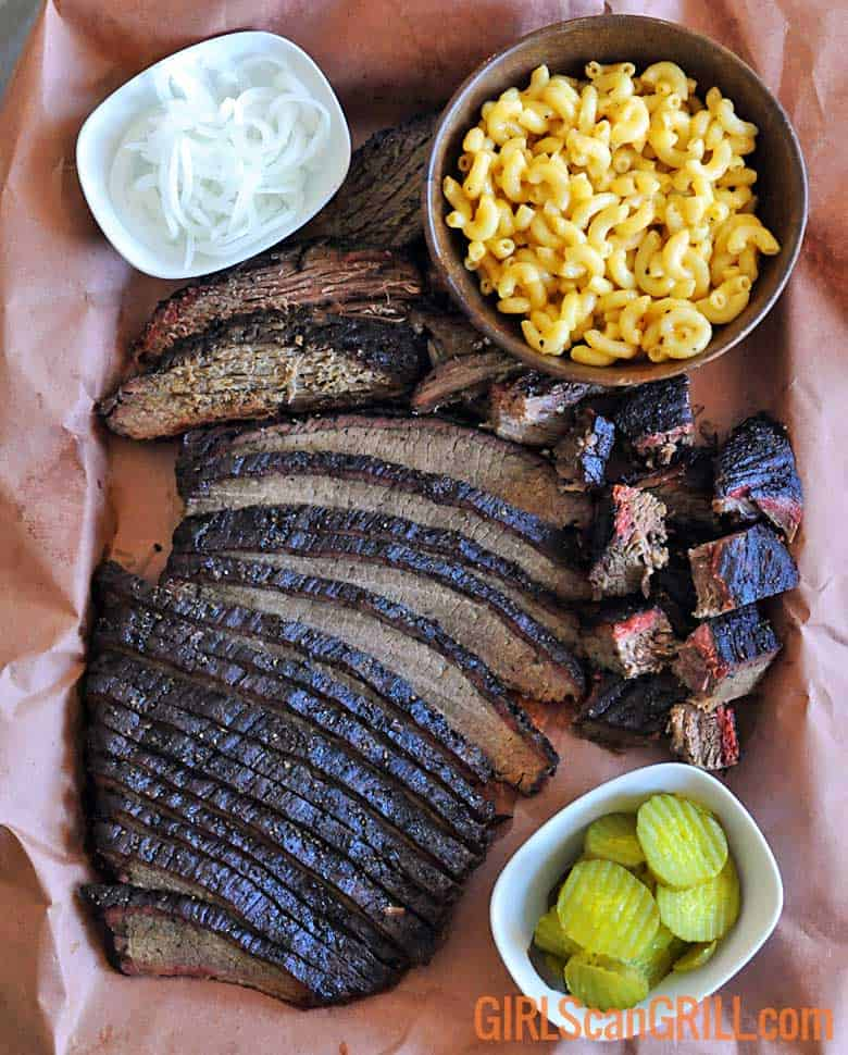 platter of sliced smoked brisket, mac and cheese and pickles