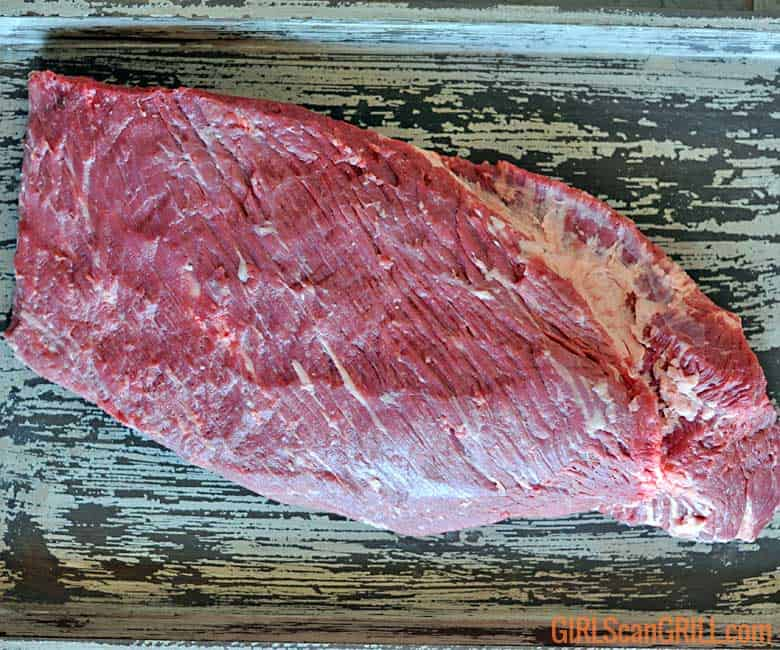 raw brisket packer on wooden platter