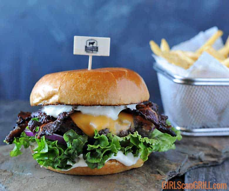 hamburger on slate with lettuce, cheese and mayo and basket of fries