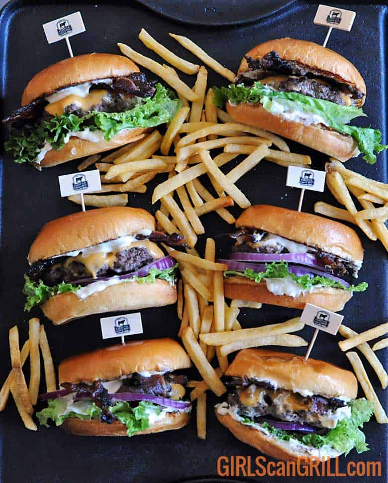 6 hamburgers on slate with lettuce, cheese and mayo and fries