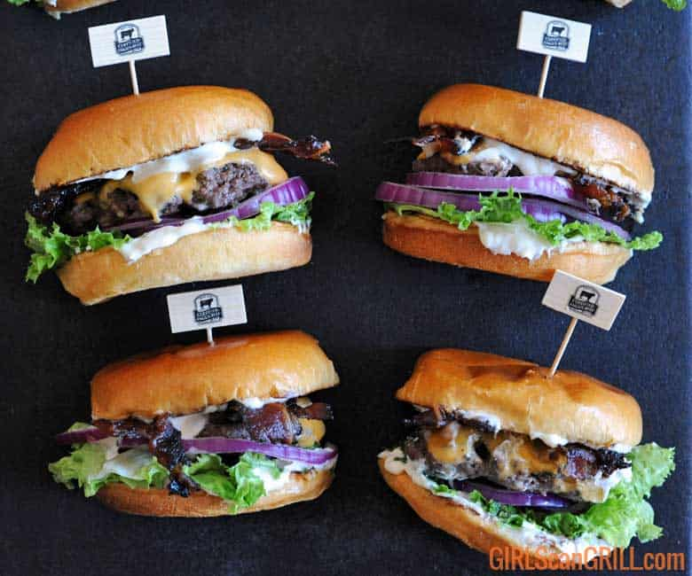 4 hamburgers on slate with lettuce, cheese and mayo