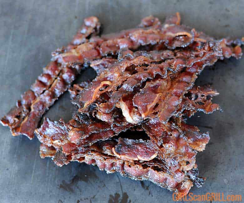 stack of cooked beef bacon and gray background