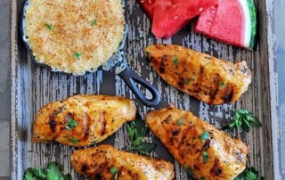 wooden platter with creamed corn in a skillet, watermelon, 4 grilled chicken breasts and potato salad