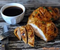 grilled sauced chicken breasts sliced on wooden platter with BBQ sauce in background