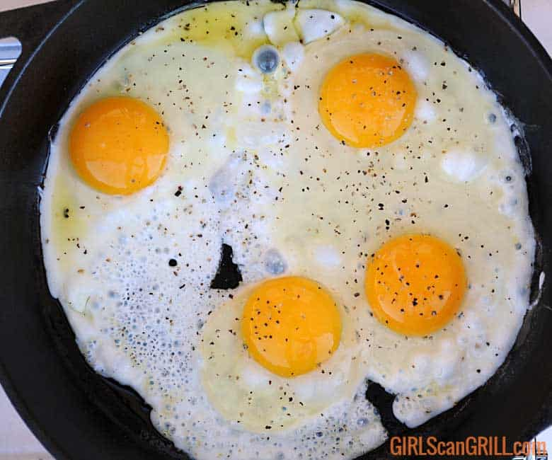 4 eggs frying in a skillet
