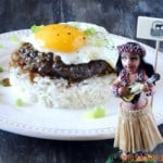 loco moco with egg on top of beef, gravy and rice with hula girl in front of plate