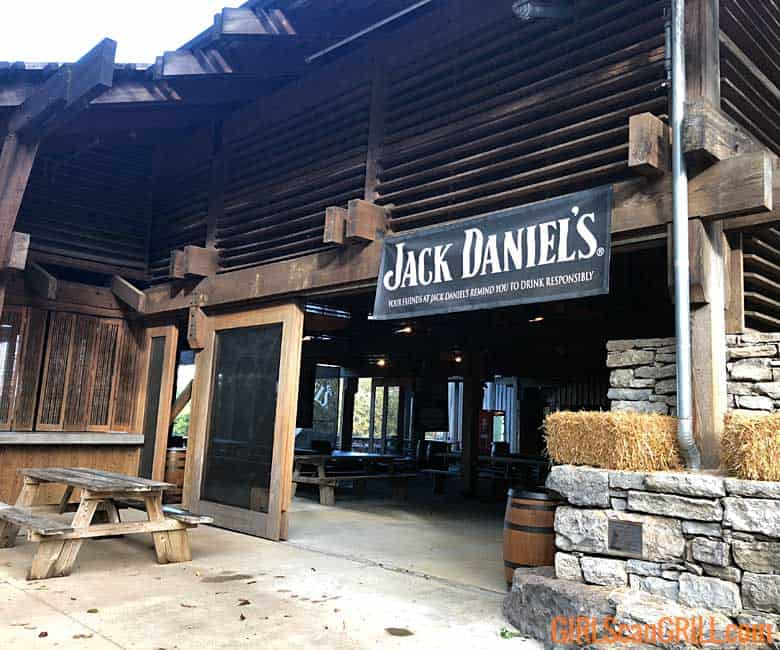 a Jack Daniel's banner hangs over the entrance to a wood and stone pavilion