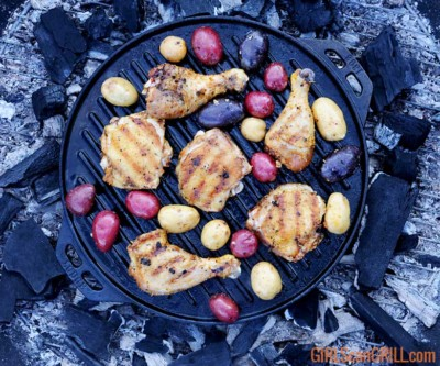 grilled chicken and potatoes in a cast iron pan over campfire