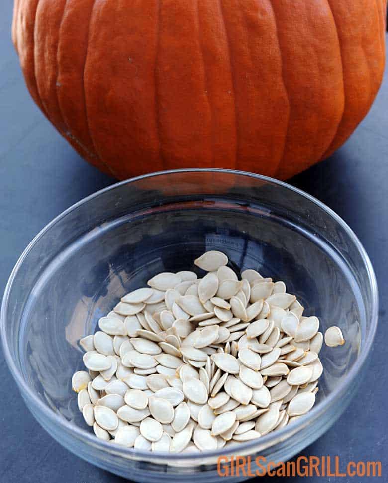 bowl of cleaned pumpkin seeds near pumpkin