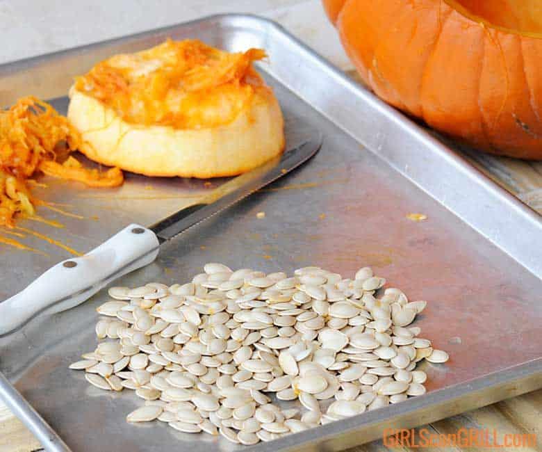 pumpkin seeds on sheet pan near carved pumpkin