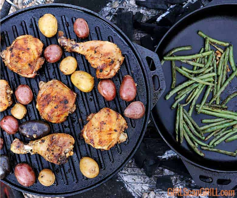 grilled chicken and potatoes in a cast iron pan near green beans