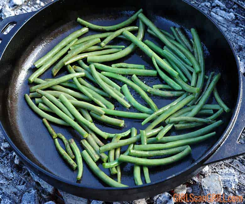 garlic green beans sauteeing in cast iron skillet