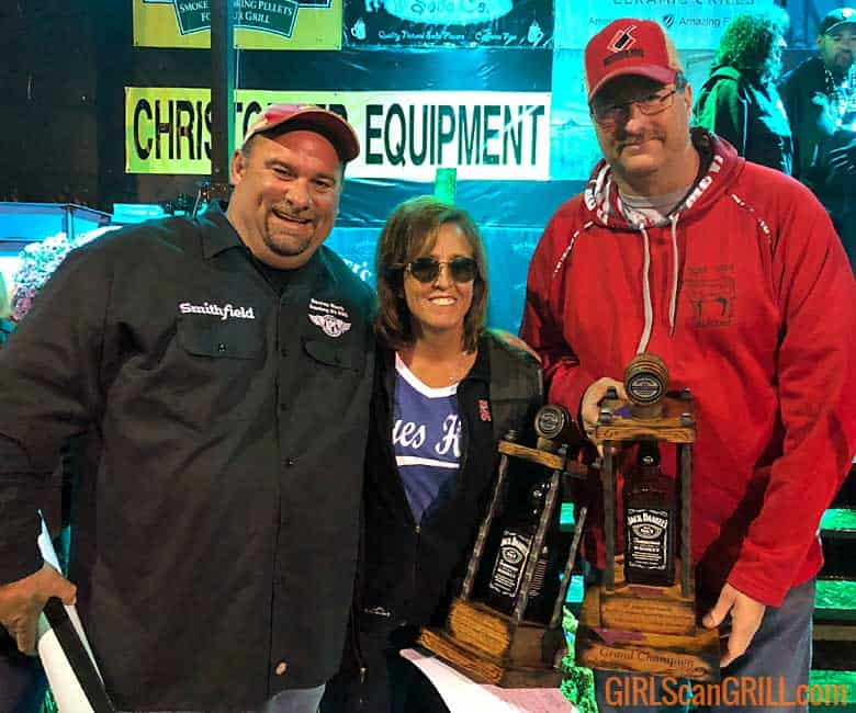 two men and a woman hold trophies