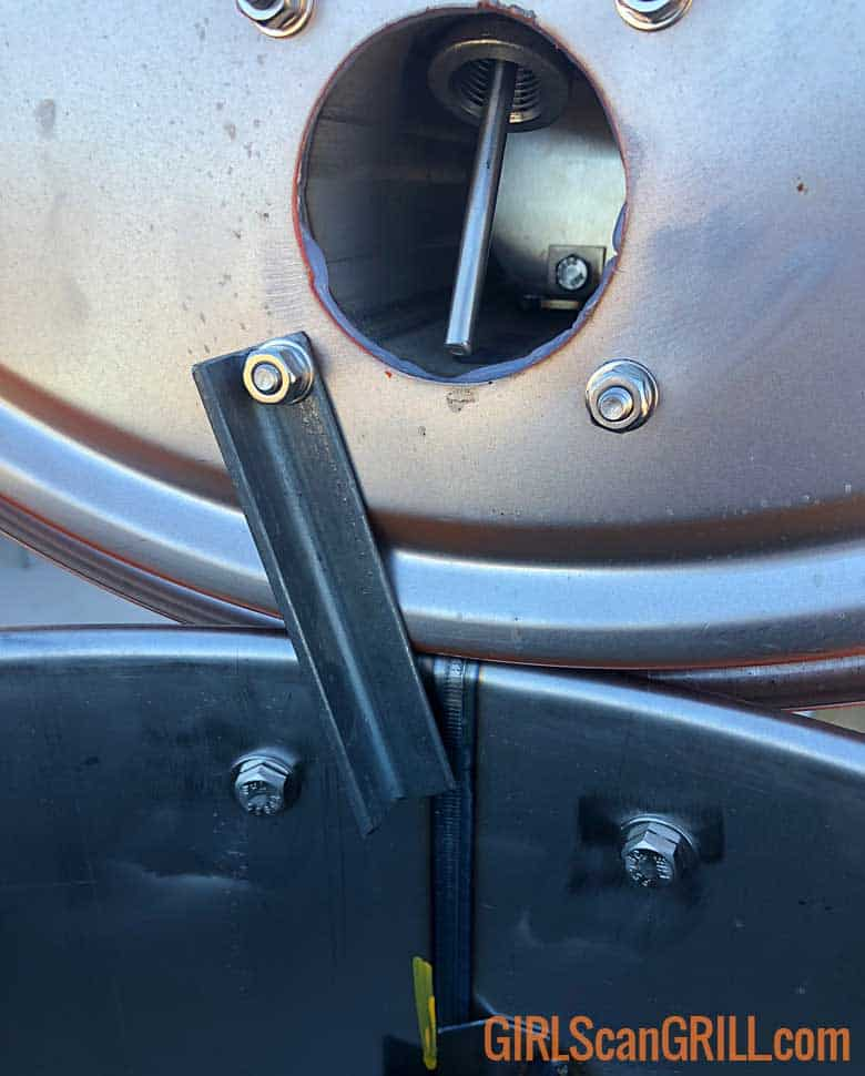 metal bar holding lid open on drum smoker