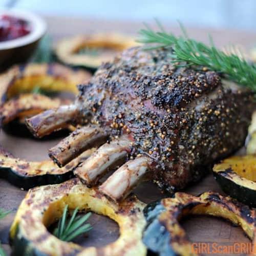 smoked pork prime rib roast on wooden platter near acorn squash slices