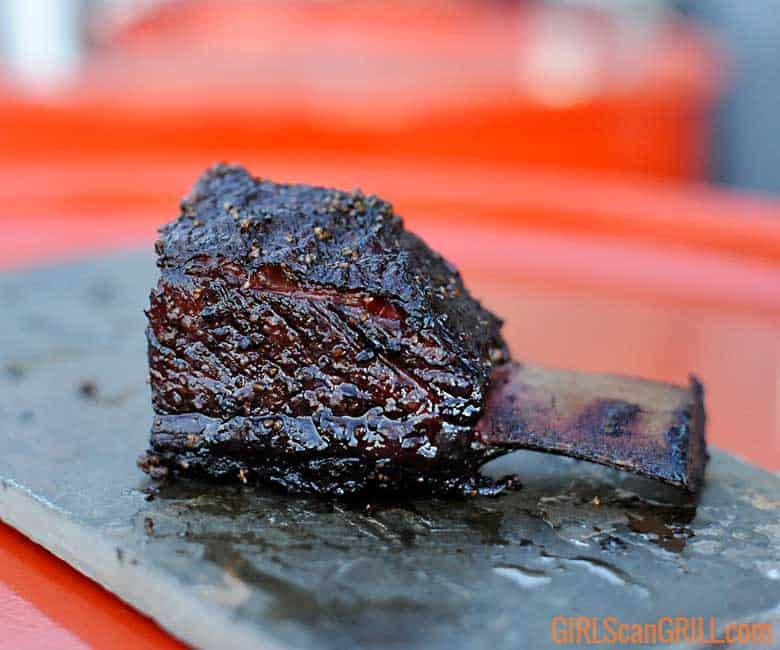 smoked short rib resting on a slate plate on an orange background